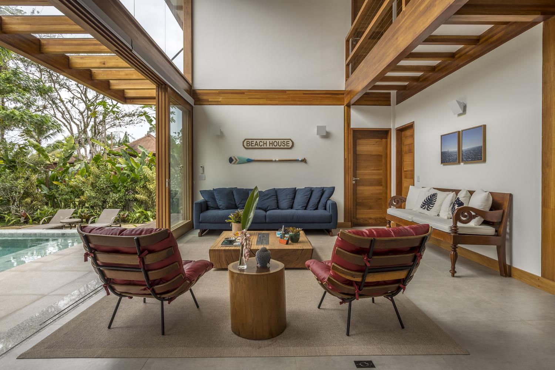 Casa com natureza ao redor, duas poltronas, um sofá e muita madeira