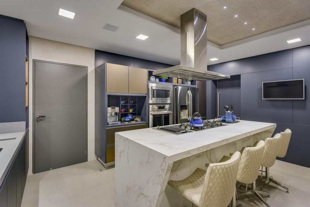 Cozinha com armários azul escuro pastel, e eletrodomésticos em inox. No centro, uma ilha com cooktop em pedra branca, com cadeiras na mesma cor