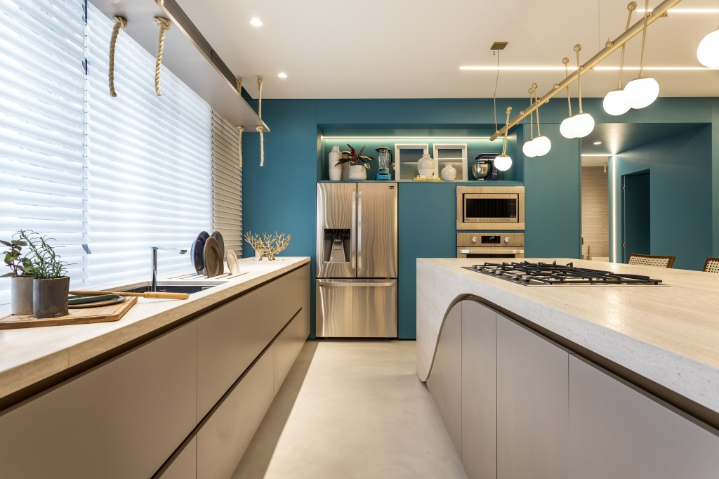Cozinha com armários azuis, eletros em inox e bancada com armários cinzas embaixo, com cooktop