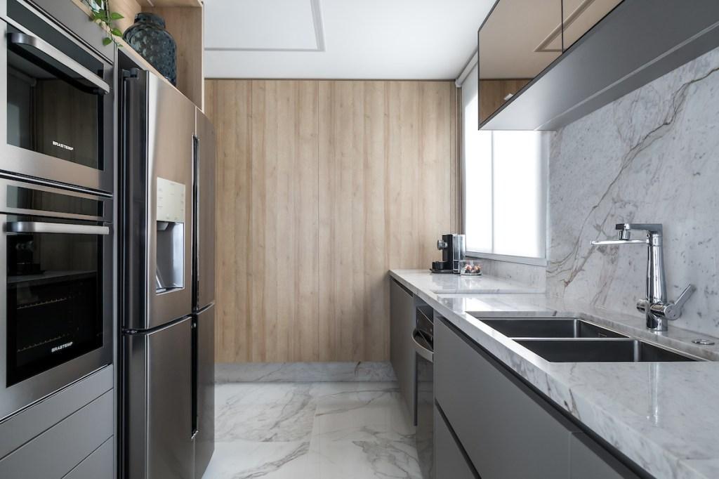 Cozinha com armários cinza e parede com revestimento de madeira