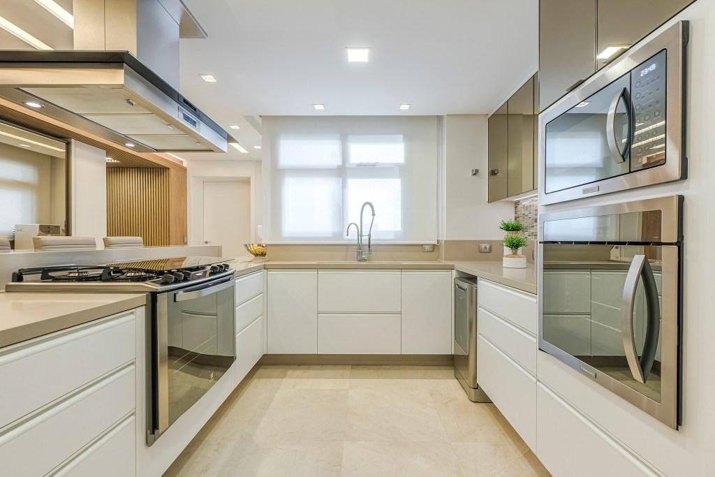 Cozinha com armários brancos, bancada da pia continua em U, feita em pedra