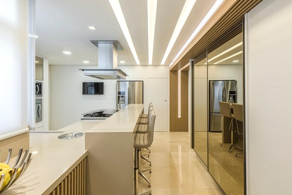 Cozinha com bancada de pedra branca, com detalhes em madeira ripada