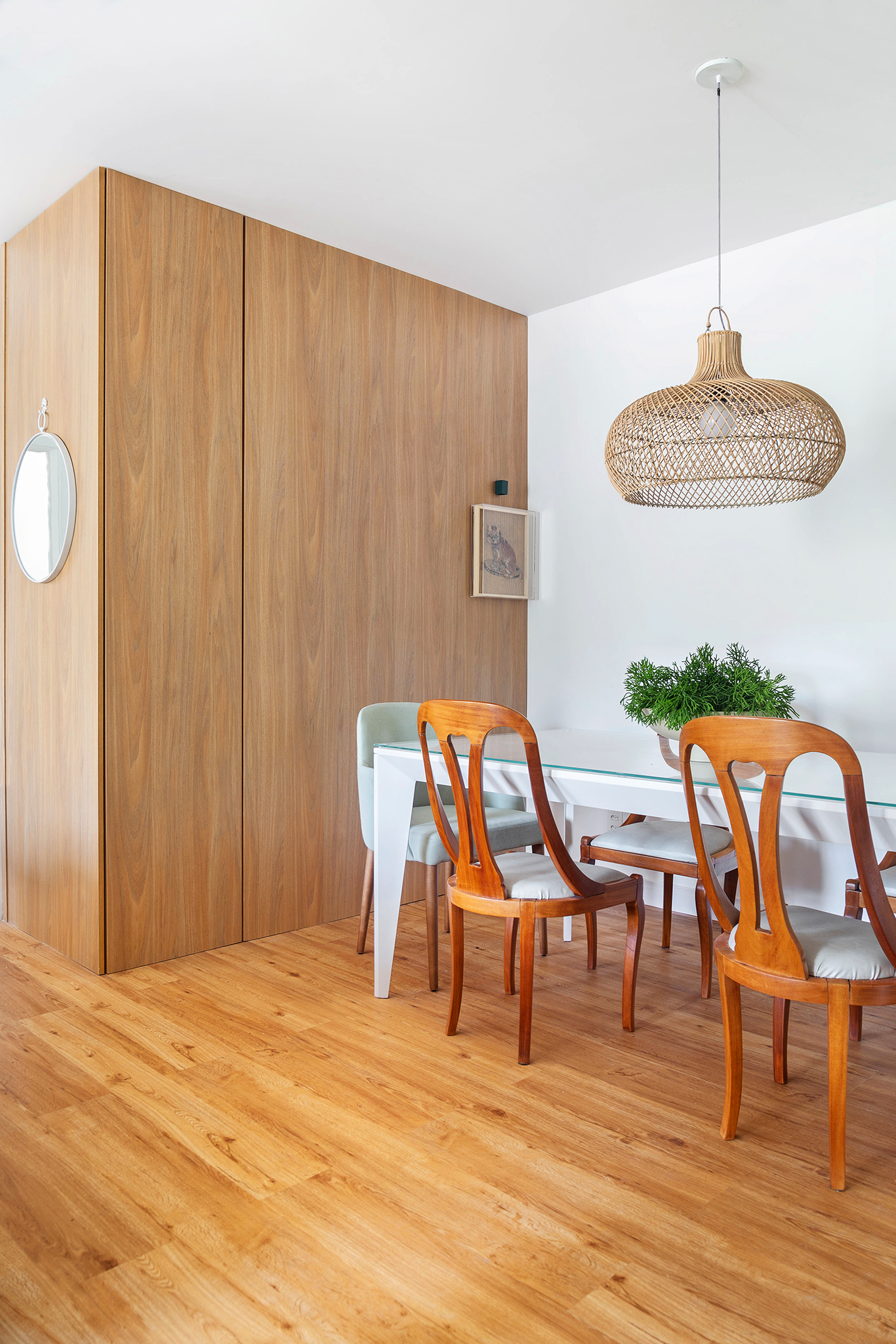 Sala de jantar com mesa de tampo de vidro e luminária pendente
