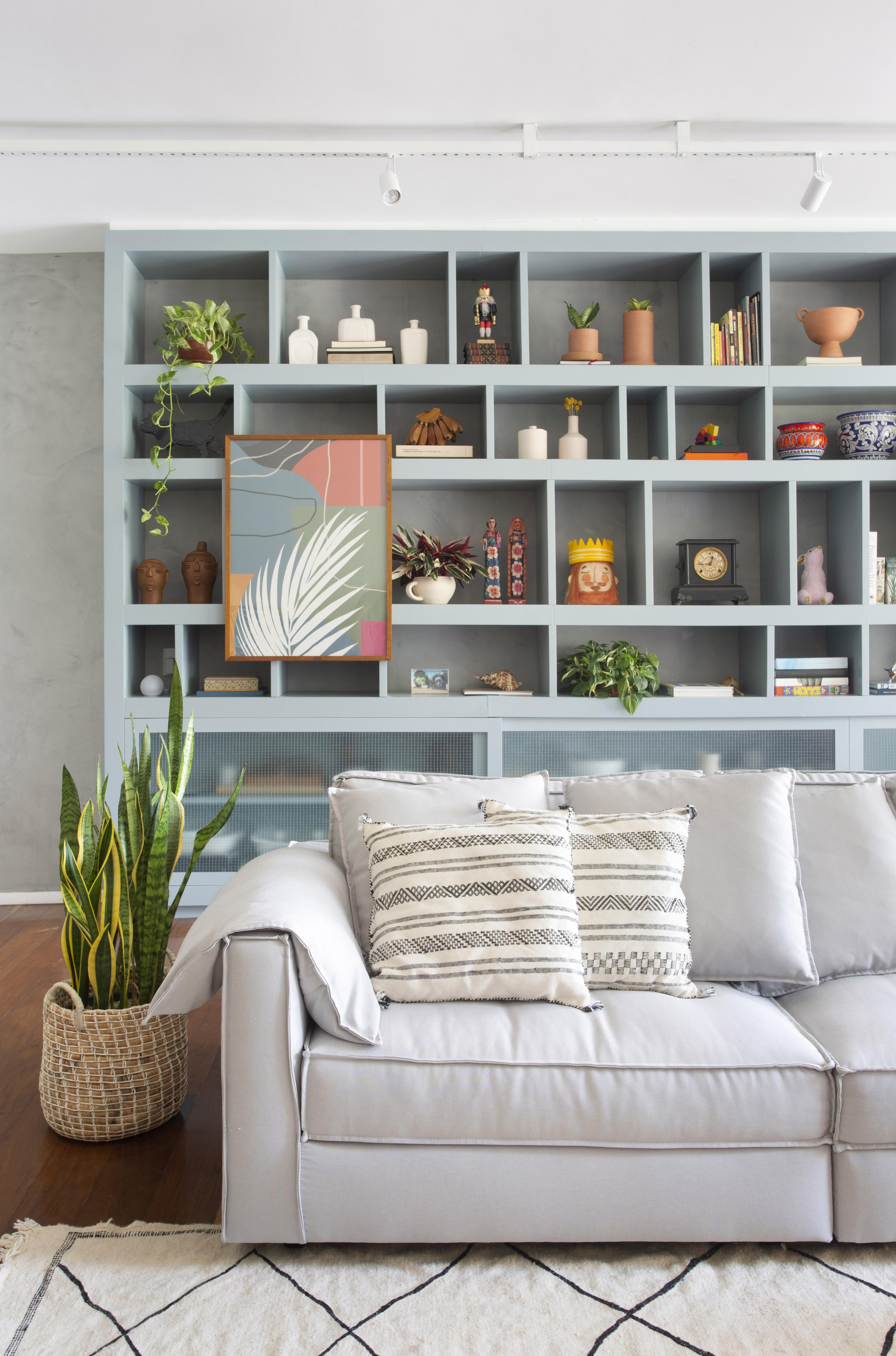 Sala de estar com estante nichada em azul e sofá de tom claro ao lado de um vaso de plantas