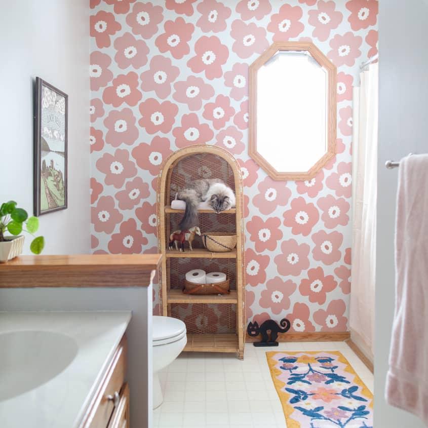 Banheiro grande com papel de parede florido em rosa salmão. Um móvel de madeira com itens de banheiro e um gato. À esquerda, a pia branca e acima do vaso, na parede branca, um quadro emoldurado