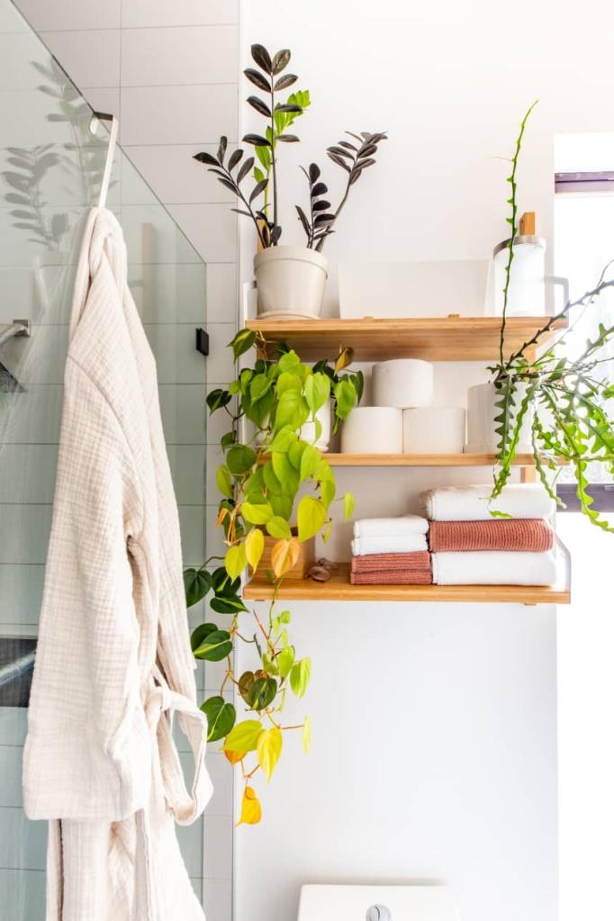 Acima do vaso, três prateleiras, com toalhas, papel higiênico e plantas. Ao lado, um roupão de banho branco pendurado