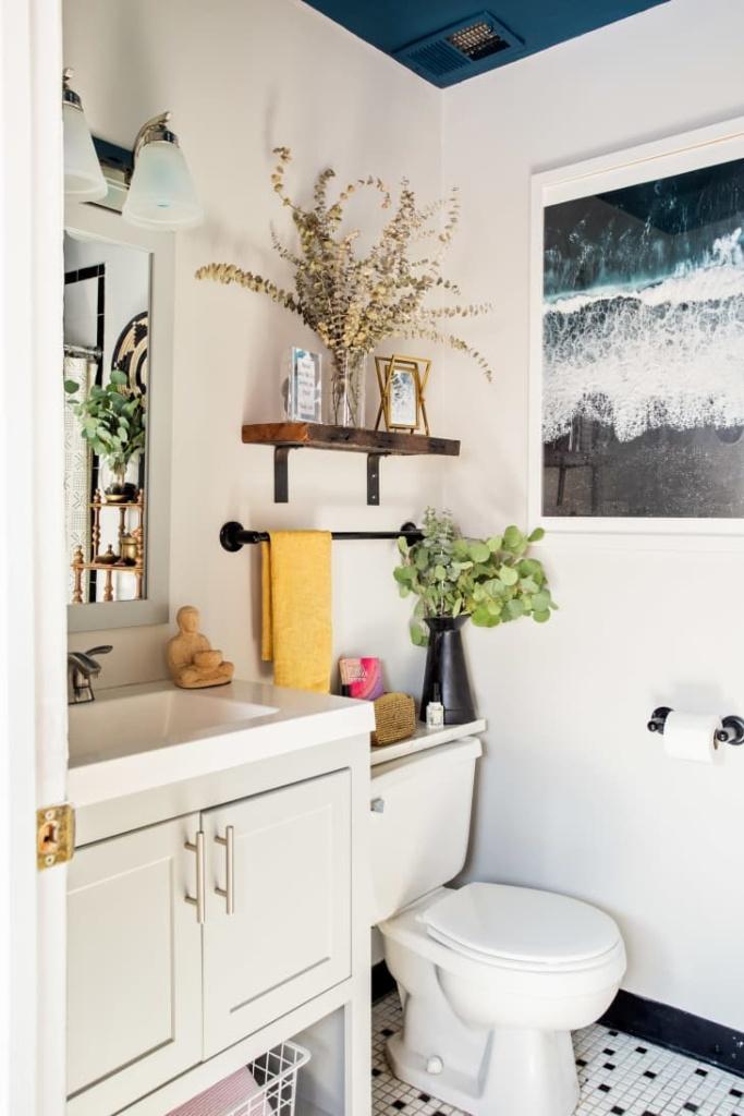 Banheiro branco, com prateleiras com porta retratos, vaso e abaixo uma haste de metal com uma toalha amarela pendurada