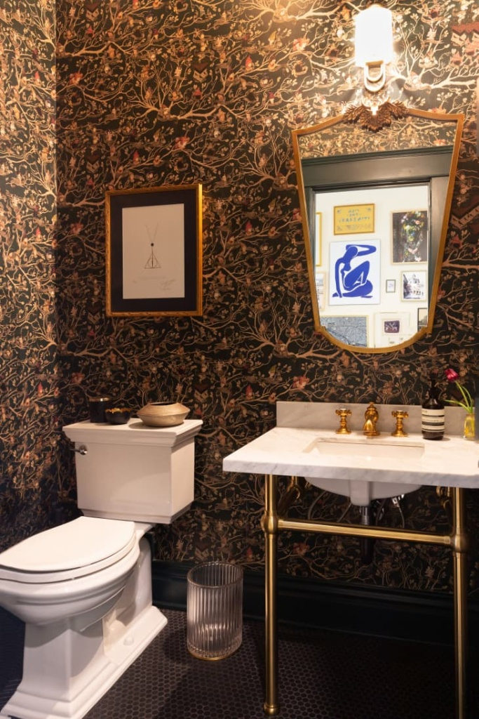 Banheiro com papel de parede escuro com ramos de árvore. Na caixa do vaso sanitário, peças de cerâmica decoram o ambiente junto com um quadro emoldurado