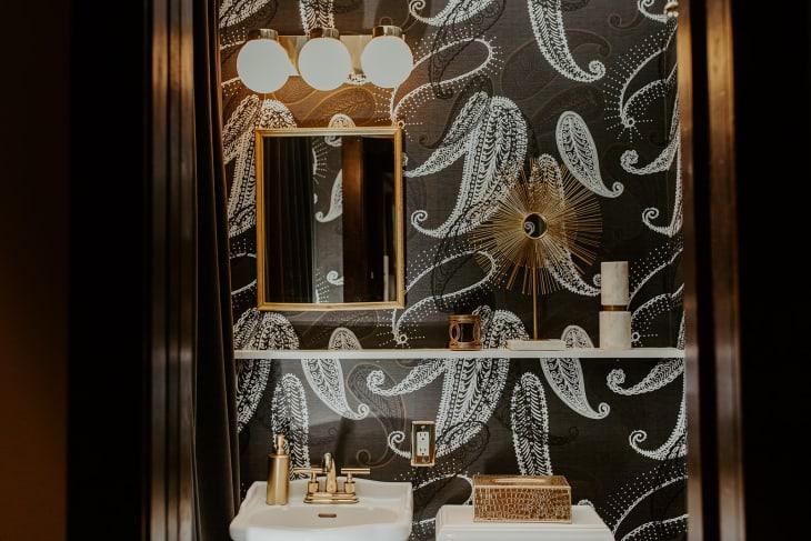 Banheiro com papel de parede escuro, com padrão de plantas. Uma prateleira longa decora o ambiente, junto com peças brancas e douradas