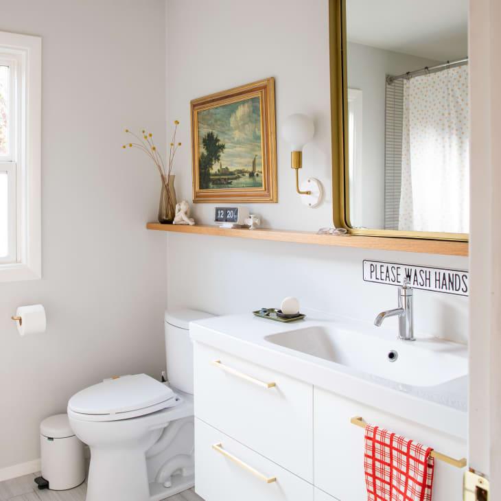 Banheiro branco, com prateleira de madeira, com vaso de flor, escultura quadro e arandela dourada