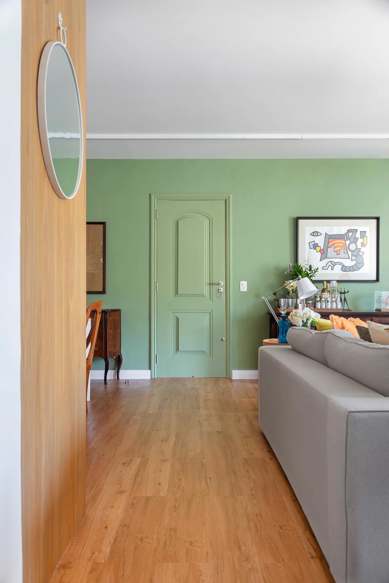 Sala de estar com parede verde claro e piso de madeira