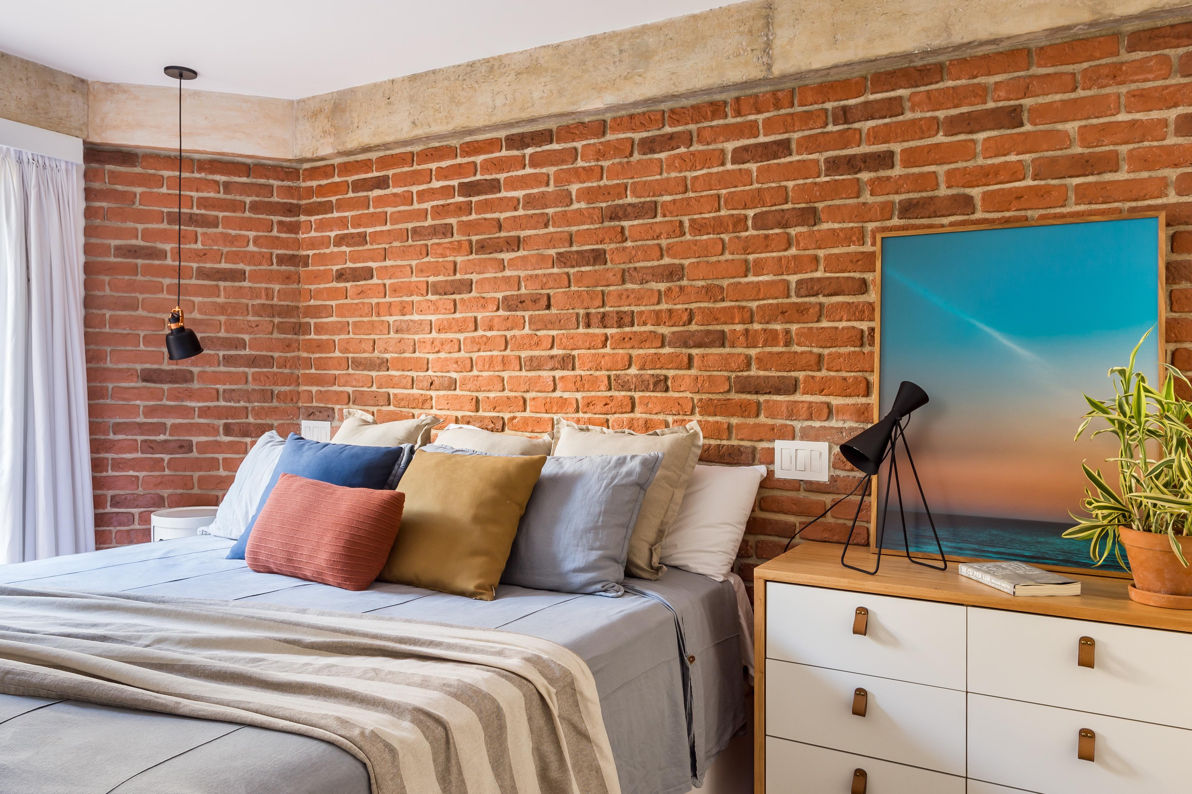 Quarto de casal com parede revestida por tijolinhos e escrivaninha branca com madeira
