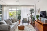 Sala de estar com muita iluminação natural. Sofá claro, piso de madeira e estante nichada em azul
