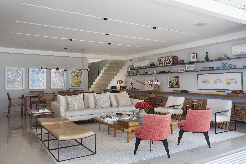 Sala de estar ampla com varanda integrada, sofá branco, poltronas vermelhas, mesa de centro