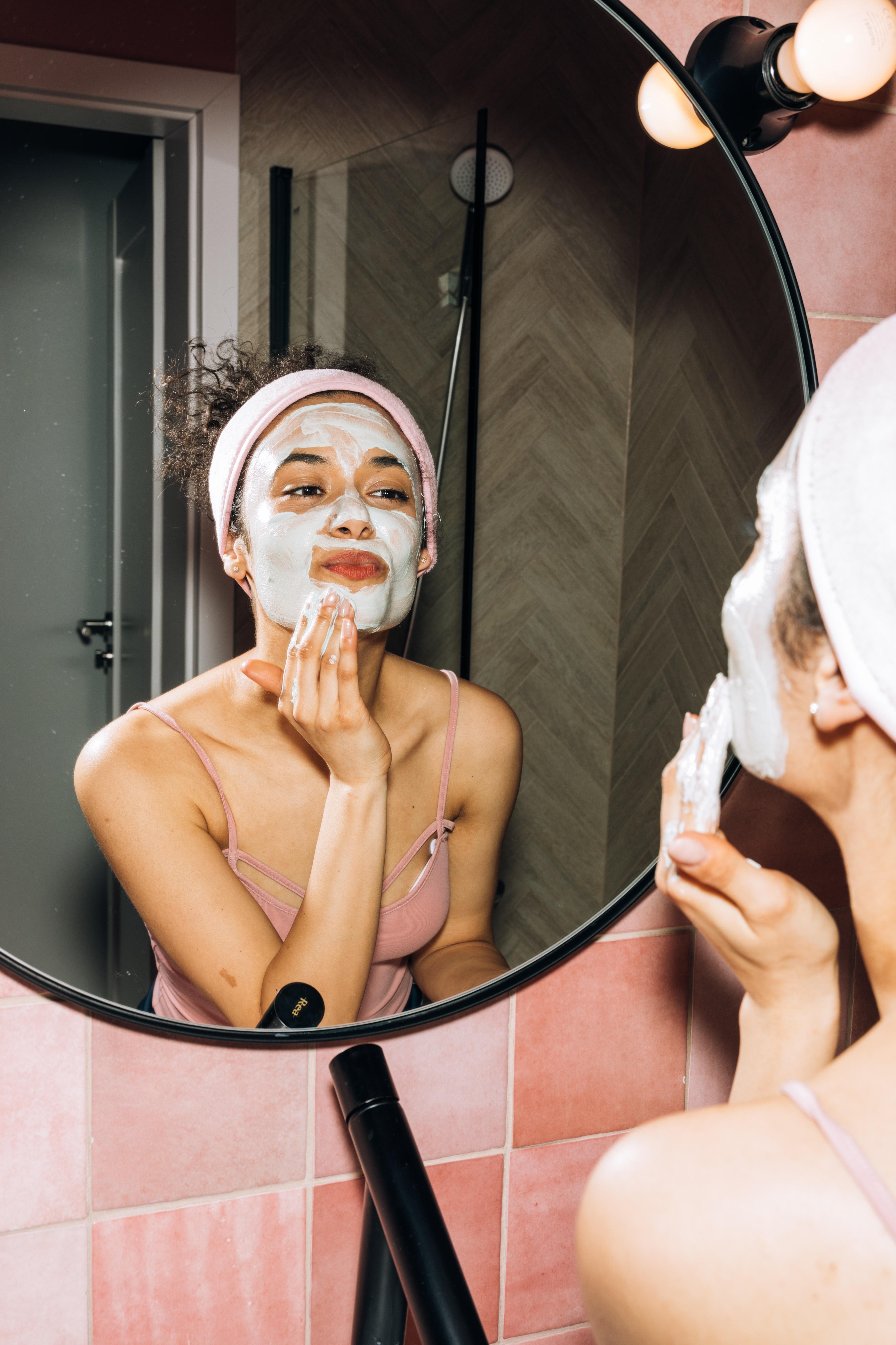 Menina fazendo máscara facial em frente a espelho