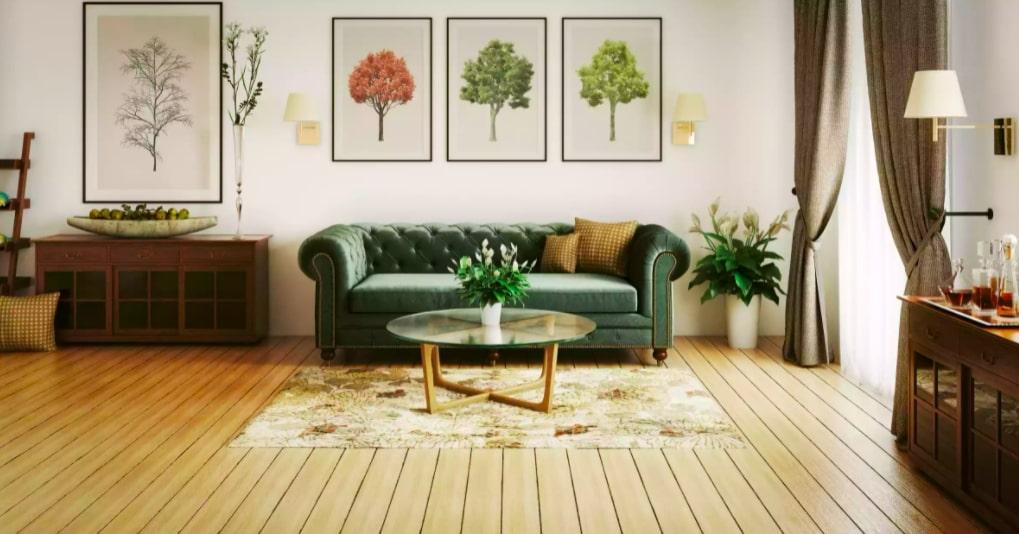Sala de estar com sofá vintage na cor verde escuro, debaixo de três quadros com árvores. Piso de madeira