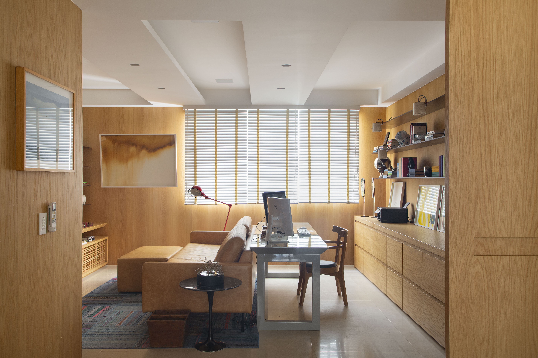 Sala de TV com home office integrado com paredes revestidas de peroba