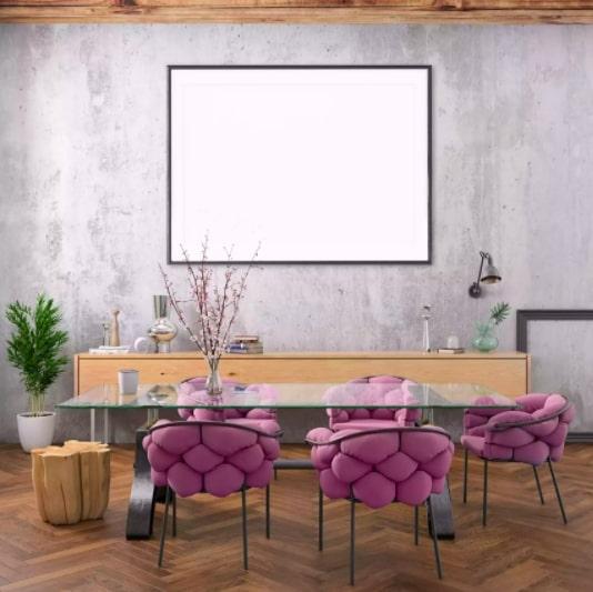 Sala de jantar com parede de cimento queimado e cadeiras de cor roxa, mesa de vidro e aparador de madeira