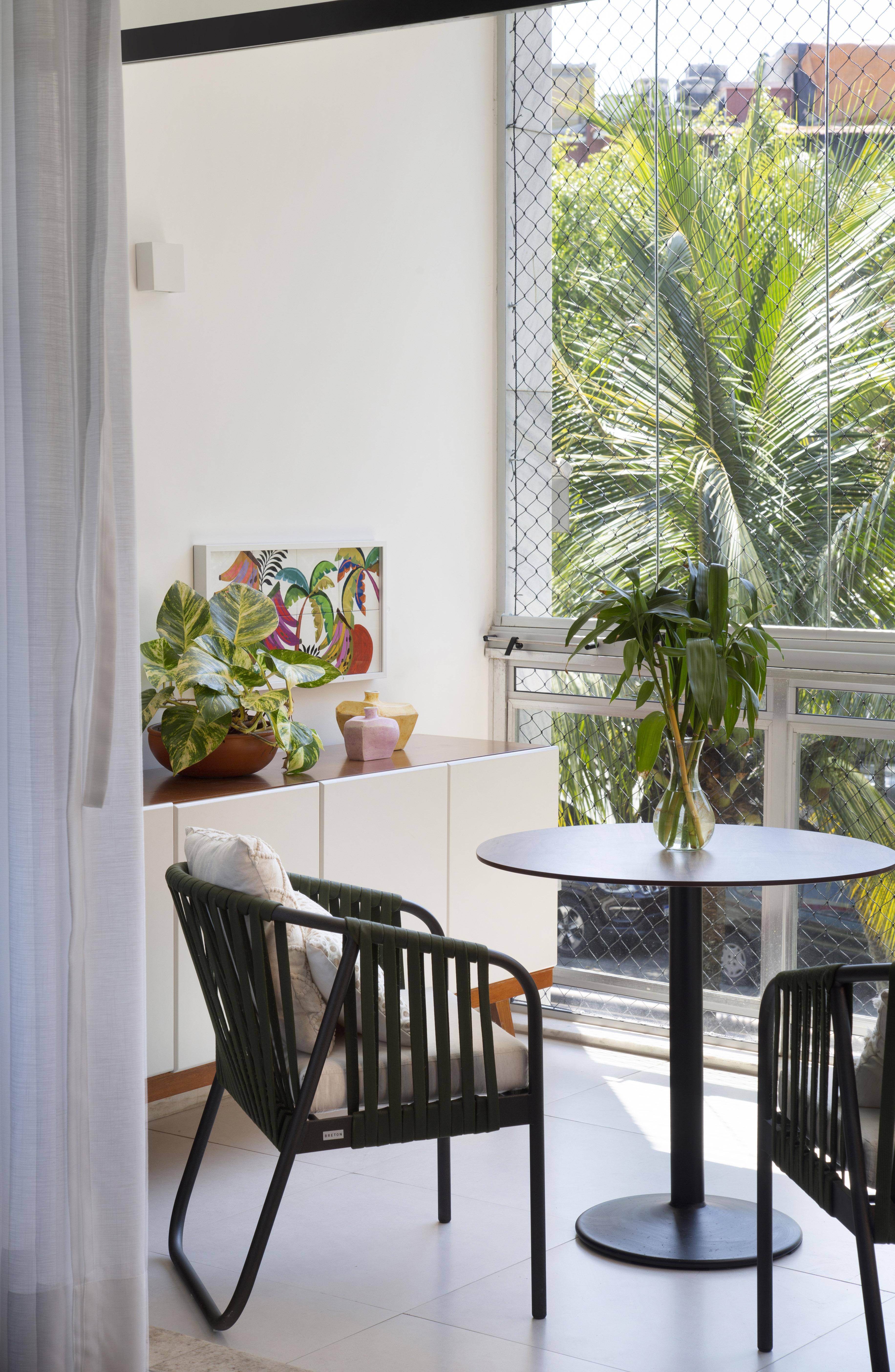 Varanda com muita iluminação natural, uma mesa e duas cadeiras pretas e algumas plantas
