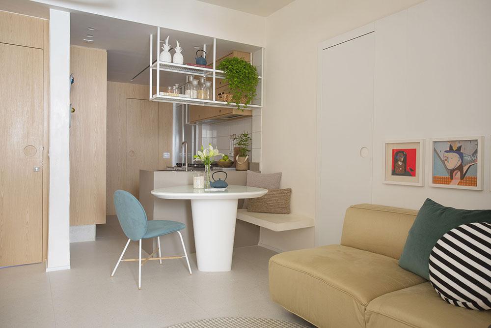 Living com sofá amarelo queimado, mesa branca redonda, cadeira azul. Piso branco e paredes com portas em madeira clara.