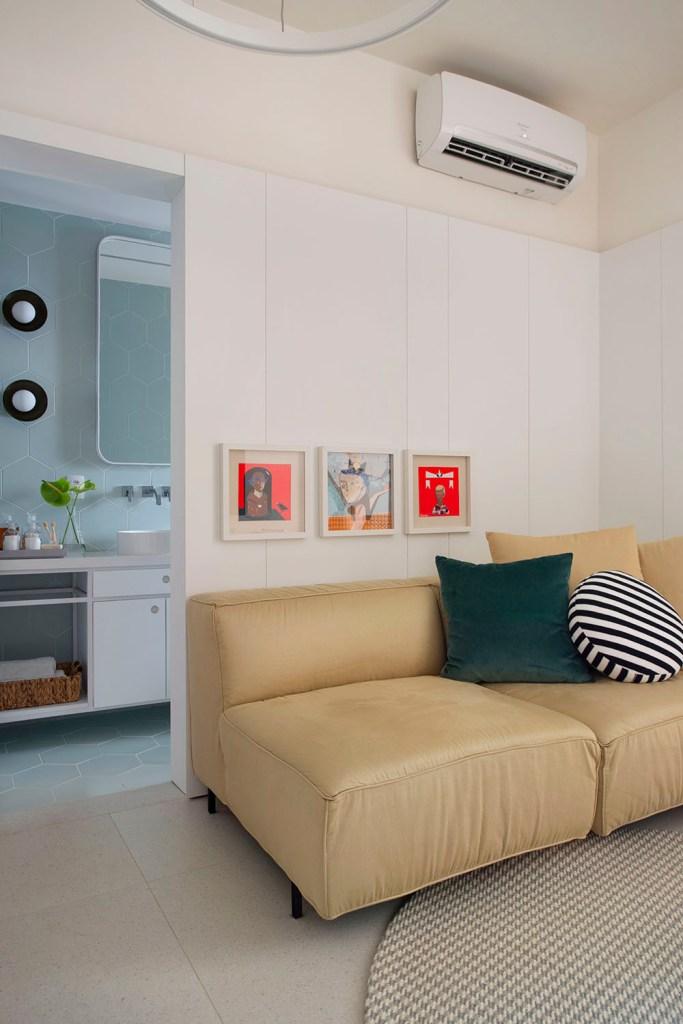 Sofá amarelo claro com três quadros quadrados pequenos acima do encosto. Almofada verde escura e almofada em forma de círculo branca e preta. Porta para o banheiro na lateral esquerda.