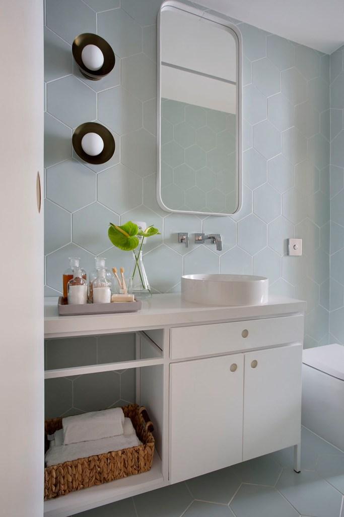 Banheiro com armários e louças brancas. Parede com revestimento de ladrilhos hexagonais azul claro pastel. Espelho retangular.