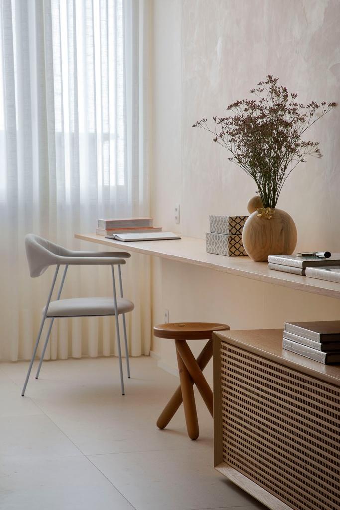 Escritório com cadeira cinza clara e linhas leves. Bancada em madeira. Vaso com flores.