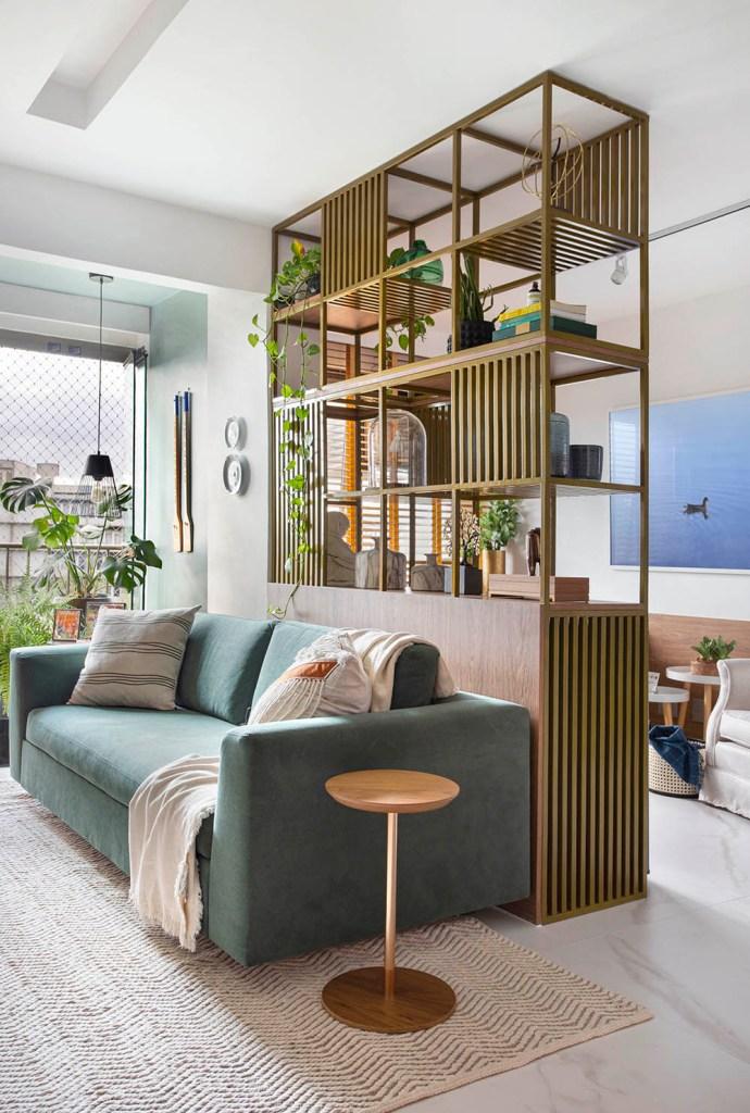 Sofá verde com almofadas brancas. Estante vazada com livros e jiboias.
