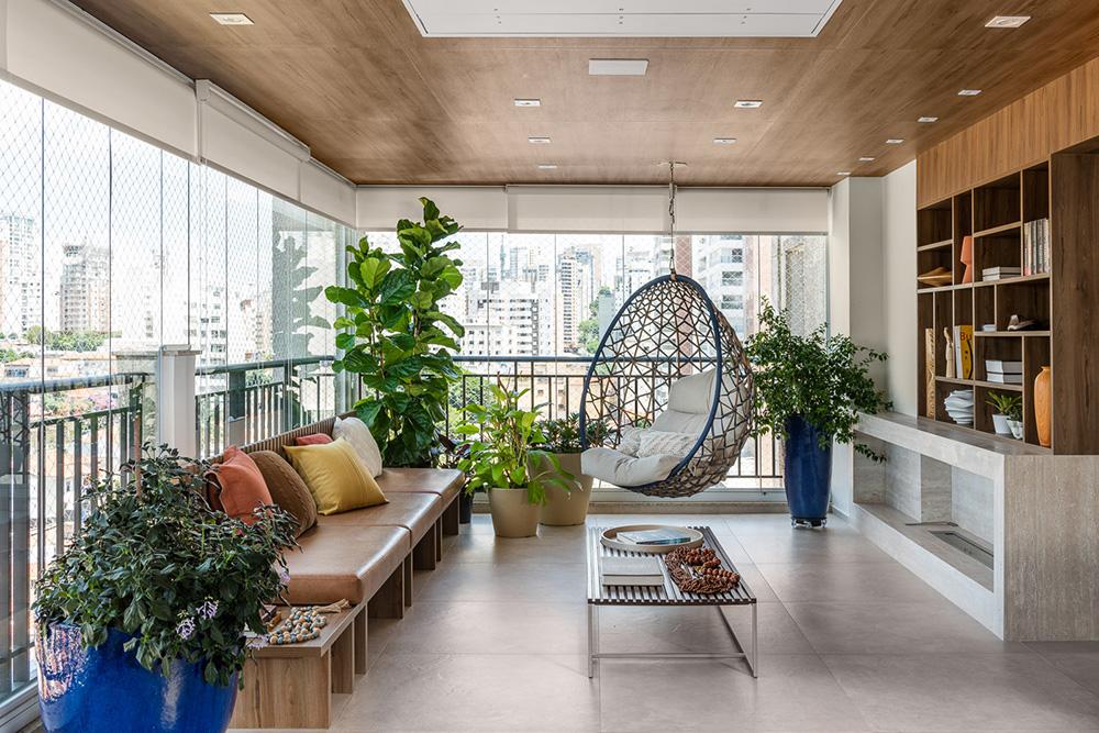 Varanda de estar com sofá, plantas, estante em madeira e balanço