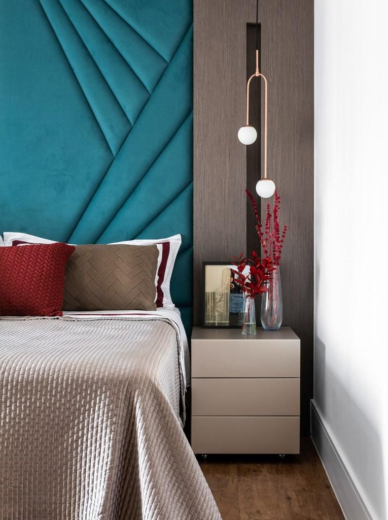 Quarto do casal. Cabeceira boisserie azul turquesa. Roupa de cama metalizada. Luminárias esféricas