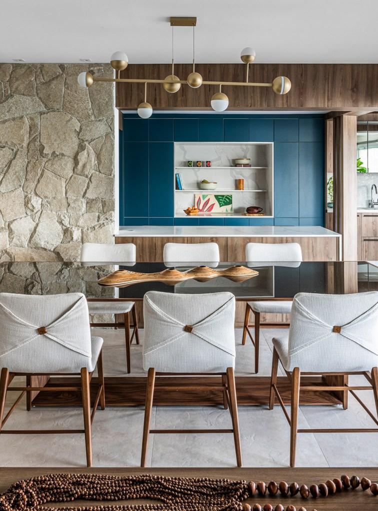 Mesa de jantar preta com cadeiras em madeira com estofado branco. Luminária Sputinik. Parede revestida com pedras ao fundo.