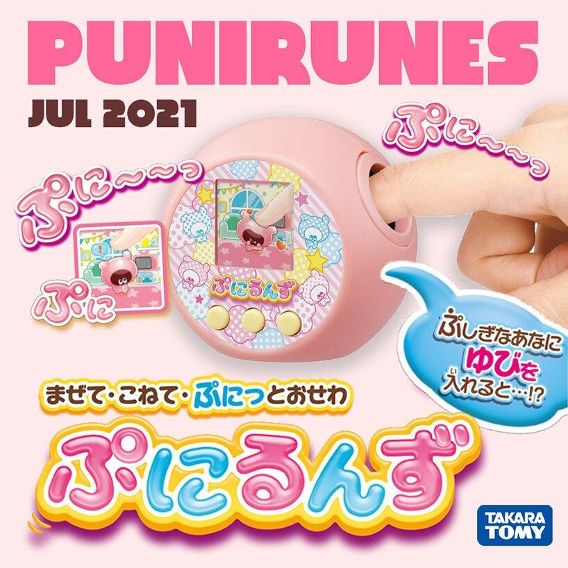Imagem promocional do punirunes, com frases em japonês, com fundo rosa. O brinquedo, também na cor rosa, aparece com um dedo ilustrando o diferencial do produto