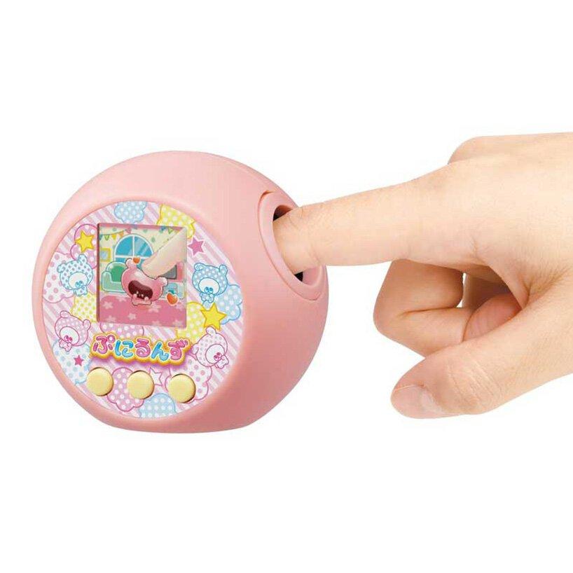 O brinquedo na cor rosa, aparece com um dedo ilustrando o diferencial do produto