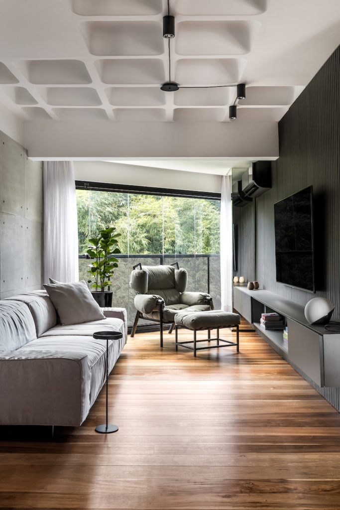 Living com parede em madeira ripada verde escura. Parede oposta em cimento. Sofá cinza e poltrona cinza. Hack preto. Janela com vista para árovres