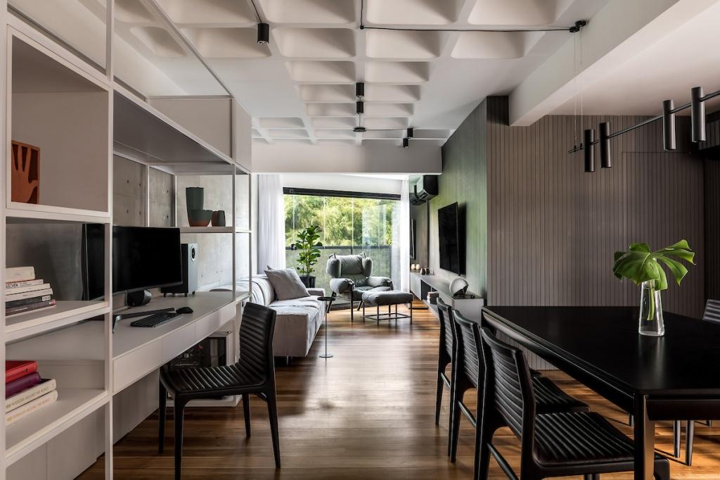 Living integrado com varanda. Piso em madeira escura. À esquerda estante vazada branca. À direita, mesa de jantar preta. Ao fundo, parede em madeira ripada verde. Sofá cinza, poltrona cinza e tv na parede