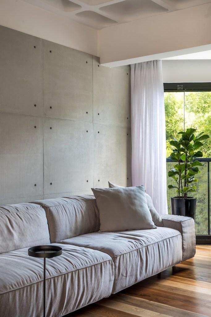 Sofá cinza com parede em concreto. Janela com vista para árvores.