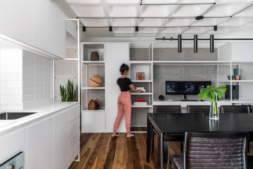 Estante em branca vazada com computador. Mesa de jantar preta. À esquerda, armários brancos da cozinha.