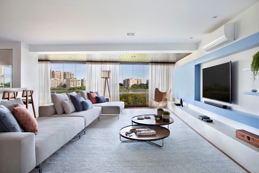 Living integrado com cozinha e área gourmet. O ambiente com cores claras tem um sofá cinza e tapete da mesma cor, com almofadas coloridas sobre o móvel e mesas de centro complementares redondas. No lado direito, a TV com painel azul claro emoldurando o aparelho. Ao fundo, a vista da varanda com vidro para a paisagem.