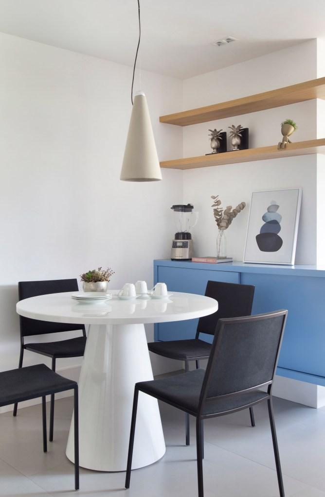 Sala com móvel azul claro, mesa circular branca e cadeiras pretas. Acima dela, um pendente cônico. Acima do móvel azul, encostado na parede, duas prateleiras de madeira clara decoram o ambiente com pequenas escultura, e flores