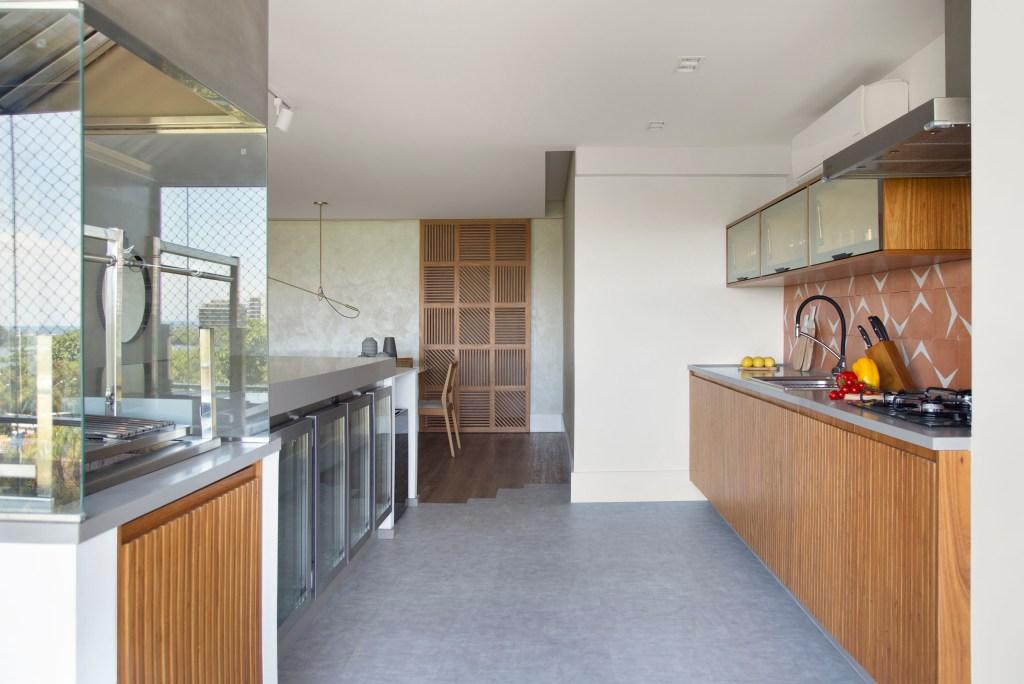 Área gourmet, com piso de cimento queimado, móveis de madeira ripada, com churrasqueira