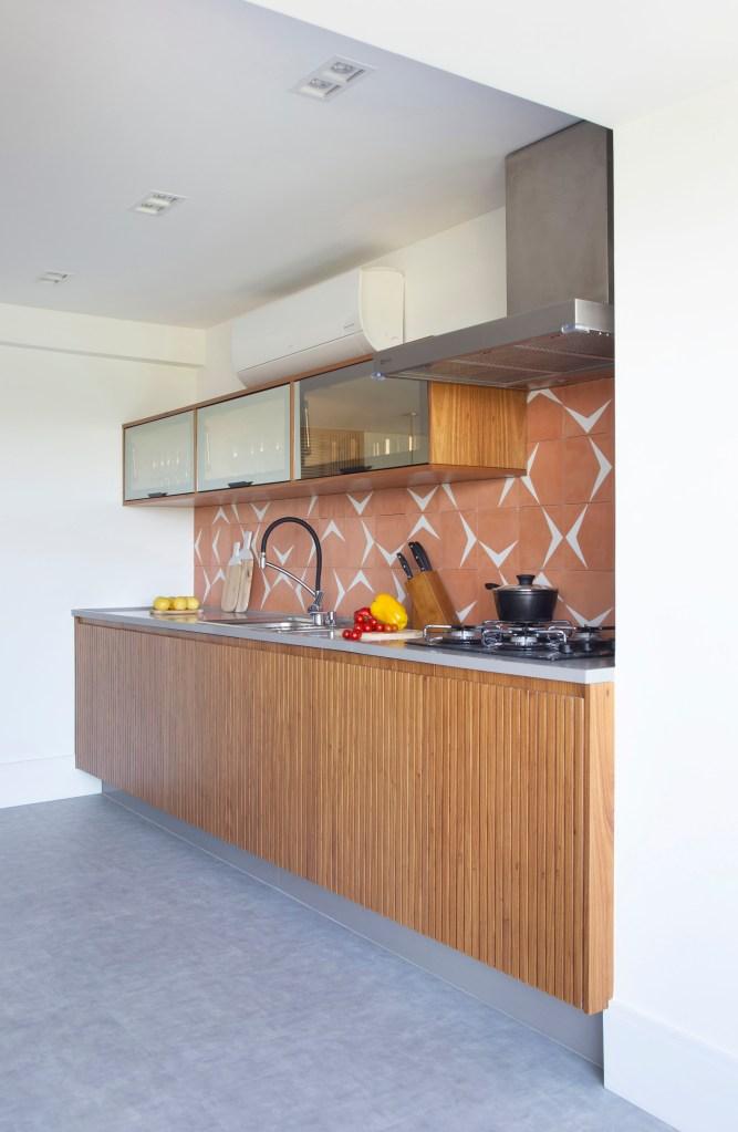 Área gourmet, com piso de cimento queimado, móveis de madeira ripada. Blacksplash na cor laranja, como tijolos