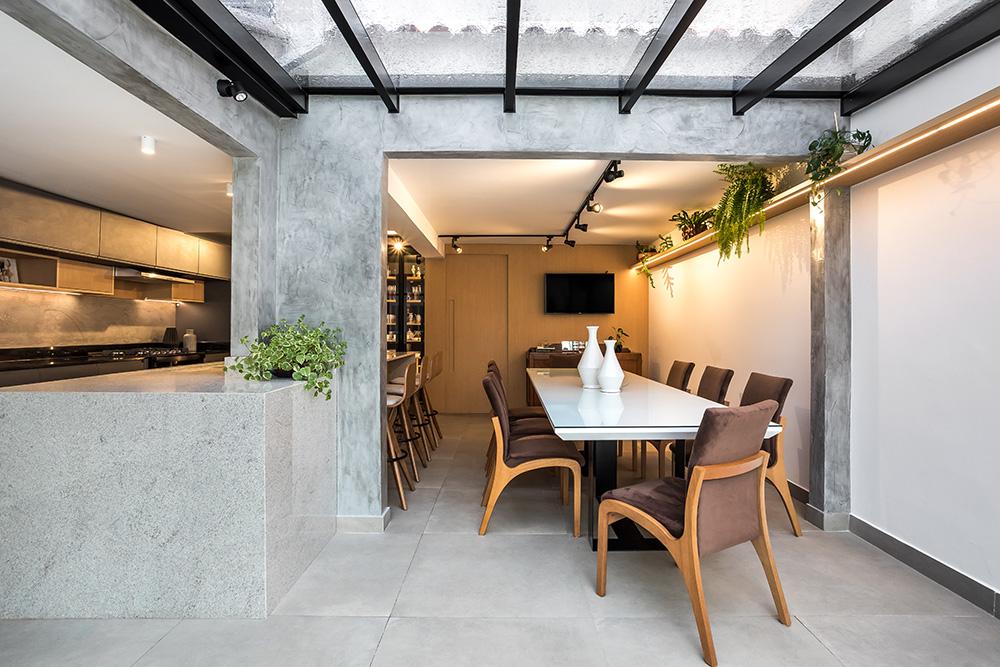 Área gourmet com piso em porcelanato cinza e paredes em concreto queimado. Pergolado transparente. Grande mesa de jantar branca com cadeiras em madeira e estofado marrom.