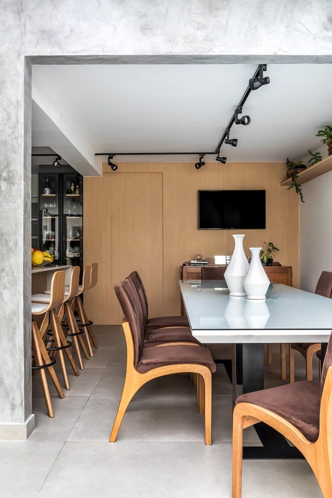 Mesa branca com cadeiras em madeira. Parede revestida em madeira ao fundo com tv pendurada. À esquerda, bancada em granito e bancos altos em madeira.