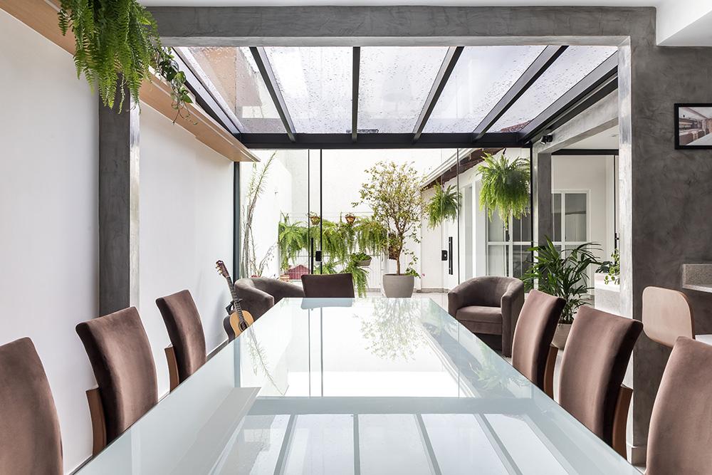 Mesa branca com cadeiras em madeira. Jardim com folhagens ao fundo.