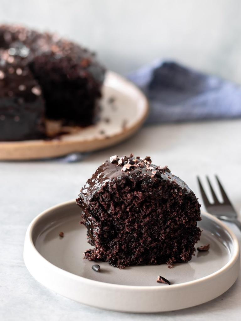 Pedaço de bolo de chocolate vegano, com cobertura de chocolate e granulado