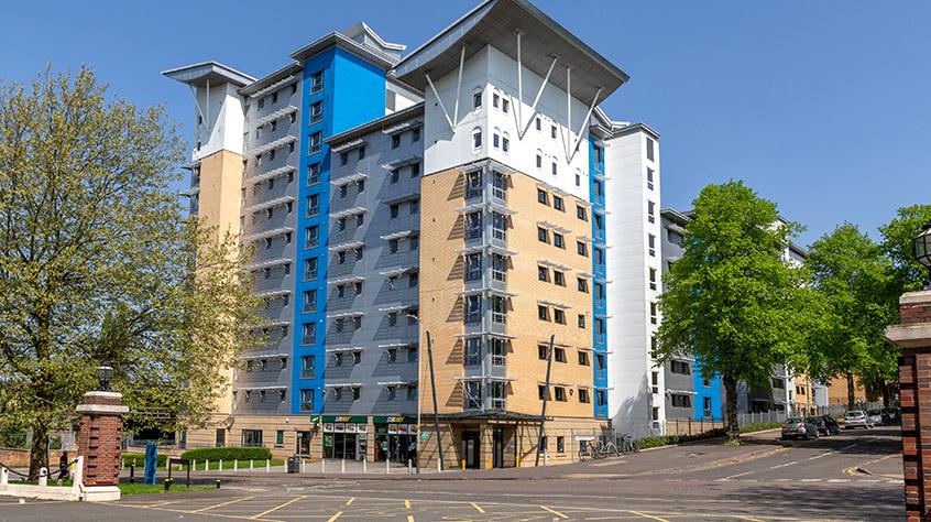 Edifício com partes amarelas, azuis, brancas e cinzas. Janelas pequenas. Teto inclinado.