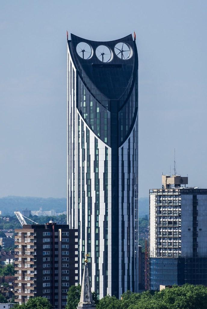 Prédio em formato de paralelepípedo de base triangular e três ventiladores no topo