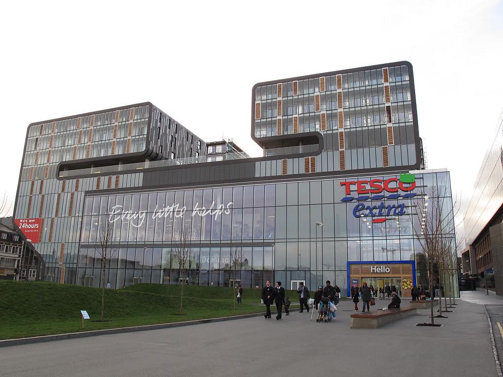 Prédio espelhado com supermercado no primeiro andar e blocos acima.