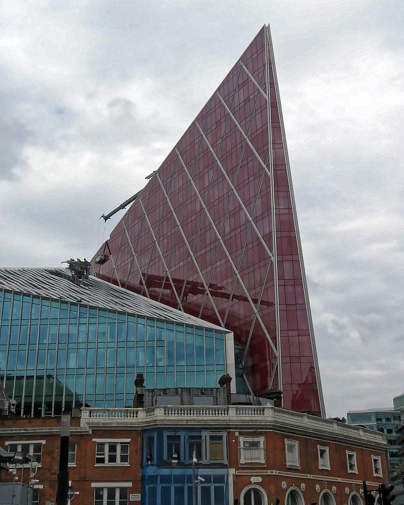 Prédio espelhado com uma grande projeção em forma de pirâmide, também espelhada, vermelha.