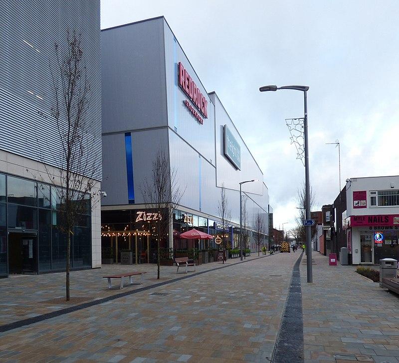 Centro de cidade vazio com grandes construções cinzas.